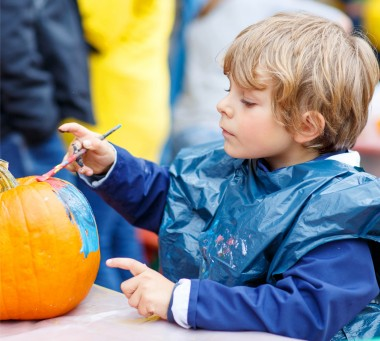 Toddler painting a pumpkin